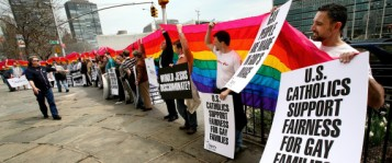 Richard Ferrara, right, of New York, holds a sign and the rainbow flag along with others during a Dignity USA demonstration Saturday, April 12, 2008 in New York, NY. Dignity USA, a Catholic gay rights group, held the demonstration across the street from the United Nations complex ahead of Pope Benedict XVI's upcoming visit to the U.S. next week. (AP Photo/Craig Ruttle)